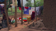 Left pan across Ugandan dooryard and three women doing chores - stock footage