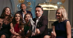 Friends holding up champagne flutes together in a toast at party - stock footage
