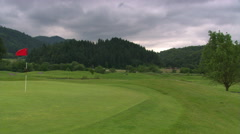 Left pan from hills under stormy sky to flag fluttering on a golf course Stock Footage