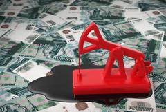 Red Pumpjack And Spilled Oil Over Russian Rubles Stock Photos