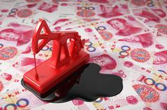 Red Pumpjack And Spilled Oil On Chinese Yuan Stock Photos
