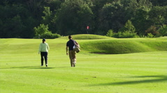 Rear view of woman golfer and her caddy walking down fairway toward flag - stock footage