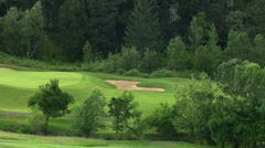 Sand trap and two-tiered green viewed from hilly vantage point above golf course Stock Footage