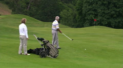 Golfer playing ball from rough, companion applauding stroke - stock footage