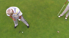 Golfer viewed from above making unsuccessful putt towards hole at right Stock Footage