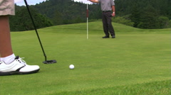 Golfer making a long putt in two strokes Stock Footage