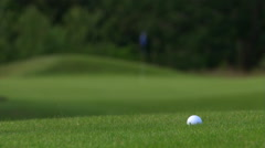 Golf ball being hit out of rough, rack focus to ball rolling on green near pin Stock Footage