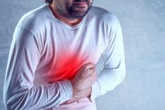 Man suffering from severe abdominal pain, hands on stomach - stock photo