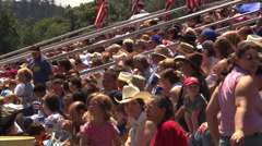 Crowd seated in bleachers at an outdoor rodeo on a hot afternoon - stock footage