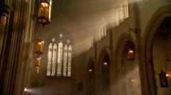 Pan across nave of empty church, tilting to sun rays through high windows Stock Footage