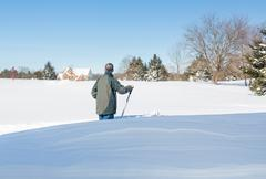 Senior adult man trying to dig out drive in snow - stock photo