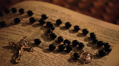 Left pan close-up of rosary lying on an open Bible Stock Footage