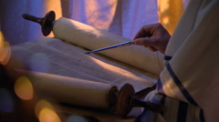 Close-up of opened Torah, reader's hand following lines with stylus - stock footage