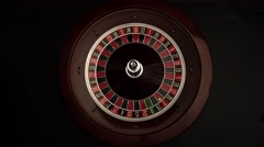 Roulette wheel is spinning slowly then stops black Stock Footage