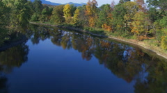 Flying down winding New England river in autumn Stock Footage