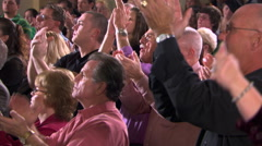 Standing congregation clapping hands above their heads - stock footage