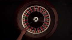 Classic roulette spinning wheel, white ball, on black Stock Footage