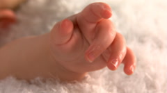 Close-up of a baby's tiny hand, left pan to baby's face Stock Footage