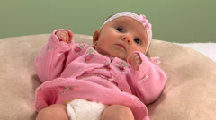 Baby in pink sweater looks at camera, moves mouth and waves arms Stock Footage