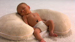 Sleeping newborn in diaper lying propped on a pillow - stock footage