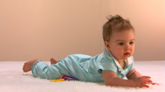 Smiling baby girl rises to hands and knees and crawls toward the left Stock Footage