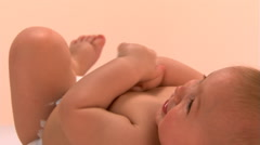 Close-up of baby lying on back, turning to face camera Stock Footage
