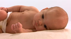 Pull-back from meditative face of baby lying on side to full-length view Stock Footage