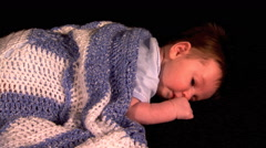 Sleepy baby lying on stomach under knitted blanket Stock Footage