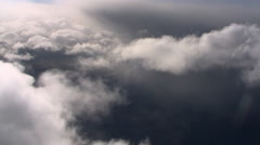 Tilting flight through wispy clouds at edge of gray cloud mass Stock Footage