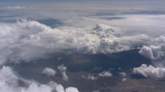 Flight over billowing cloud masses with arid terrain below - stock footage
