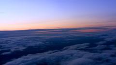 Sunset flight over broken cloud layer over rugged terrain, passenger POV Stock Footage