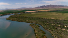 Flight above the Colorado River and a riverside community near agricultural land Stock Footage