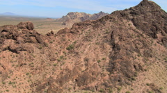Flight over rocky ridge to wide view of desert landscape Stock Footage