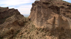 Flying through a notch in sandstone cliffs to reveal a wide valley. Shot in - stock footage