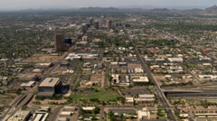 High aerial approach to Phoenix skyscrapers with mountains in background. Shot Stock Footage