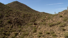 Low flight over cactus and jumbled rocks to wide view of rugged desert hills. - stock footage