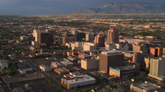 Stock Video Footage of Flying past downtown Albuquerque with Sandia Mountains in background. Shot in