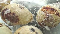 Quail eggs under boiling water surface macro video Stock Footage