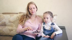 Mother and daughter eat chocolate and watch TV Stock Footage