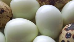 Dolly video of unshelled hard boiled and shelled quail eggs Stock Footage