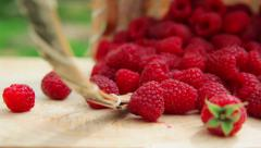 Ripe raspberries scattered from the basket on the table Stock Footage