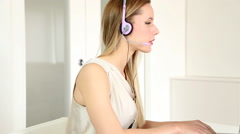 Beautiful young blond telesales woman with headphones on computer talking to - stock footage
