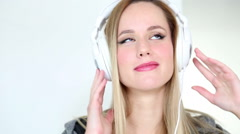 Beautiful young blond woman dancing with white headphones Stock Footage