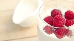 Raspberry in a glass of milk. Milk shake Stock Footage