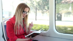 Beautiful woman riding tram, while reading book - stock footage