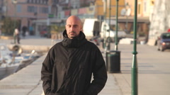 Man in black jacket walking along harbour Stock Footage