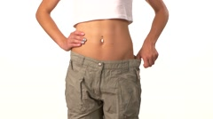 Sporty girl in big trousers, showing her lose weight, on white Stock Footage