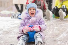 Five-year girl with a happy cry slipping ice slides Stock Photos