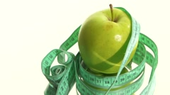 Green apple with measuring tape on white, rotation, reflection Stock Footage