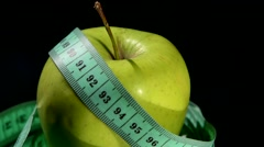 Green, fresh apple with measuring tape on black, rotation, reflection, close up Stock Footage